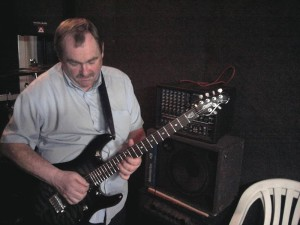middle-aged man playing the electric guitar.