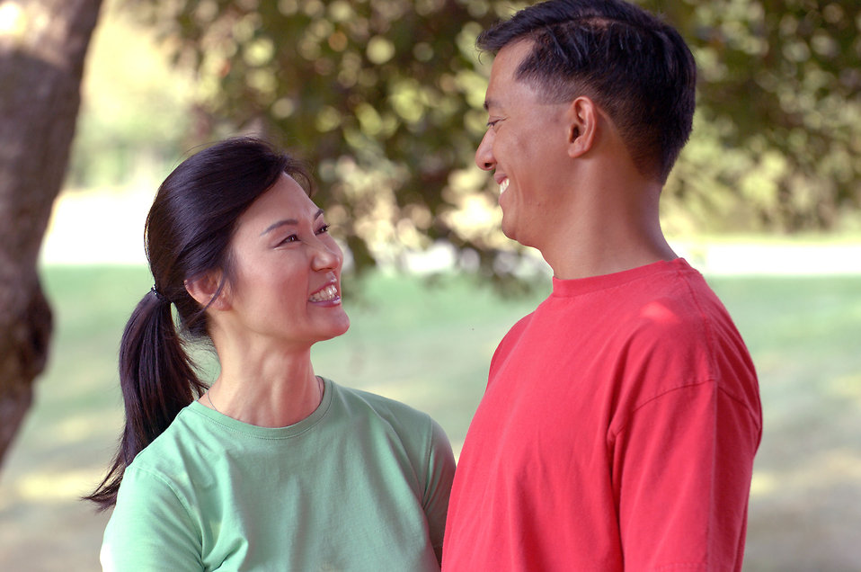 Happy Asian-American couple smiling at each other.
