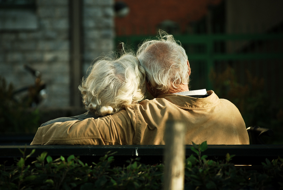 Elder couple sitting and cuddling on a park bench. Image is taken from behind them.