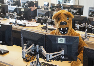 Photo of a person in a lion mascot uniform sitting in a computer lab