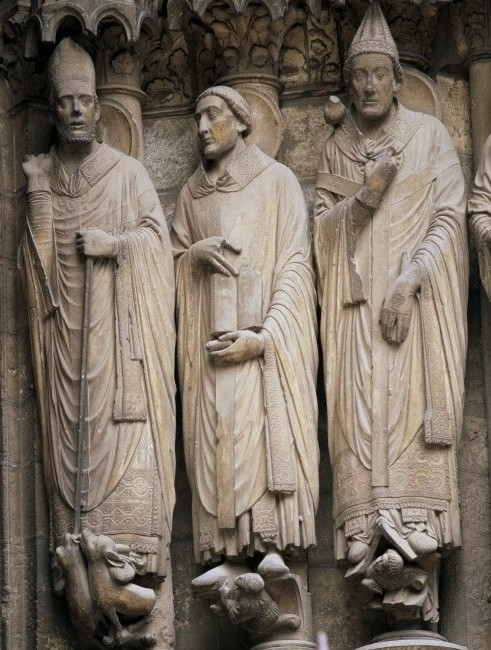 A sculpture of three saints. The saints are a part of the wall they are carved from. None of their arms extend out from their forms; the sculptures are all very solid.