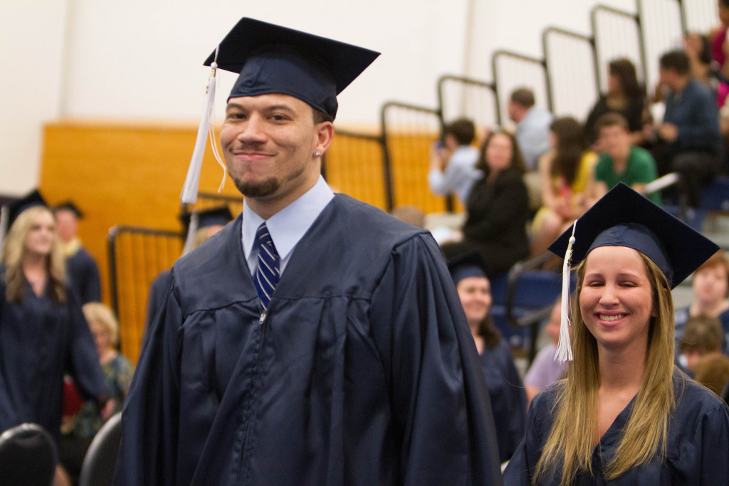 Photo of two students wearing caps and gowns, at graduation.