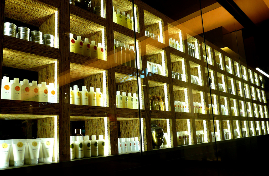 Photo of row of salon shelves full of hair-care products.