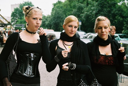 Photo of three young women dressed in Goth outfits walking outside in a city.