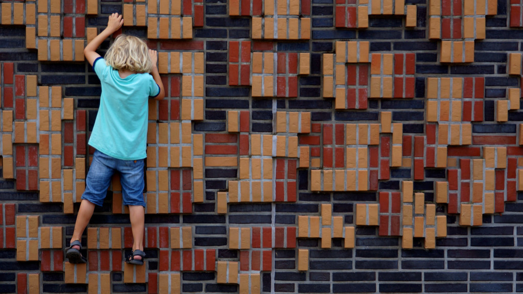Photo of a child climbing a brightly colored brick wall.