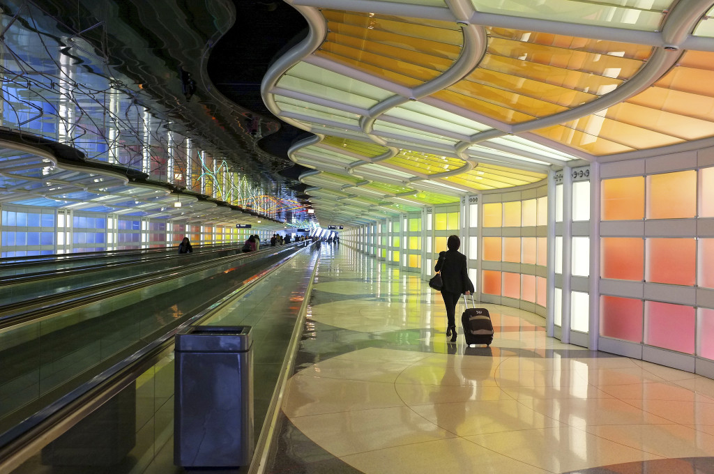 Photo of a lone traveler pulling her suitcase, walking through brightly colored O'Hare Airport
