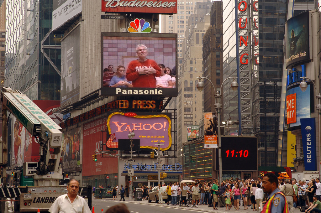Photo of Times Square in New York City. At center are two large, lighted billboards advertising Panasonic and Yahoo.