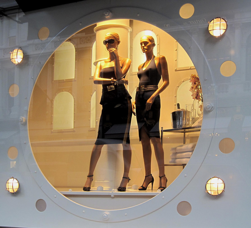 Photo of two female manikins wearing black dresses in a Ralph Lauren display window.