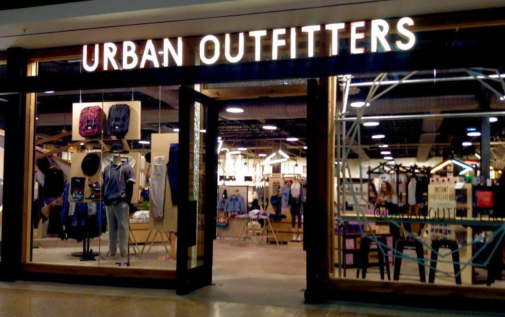A storefront for Urban Outfitters. Near the front of the store are mannequins wearing the store's clothing. The inside of the store has industrial spotlights, a cement floor, aisles of clothing, and more mannequins.