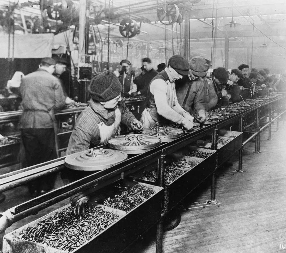 An old photograph of people building hubcaps on an assembly line.