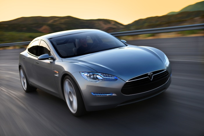 Photo of Tesla Model S being driven on a country road.