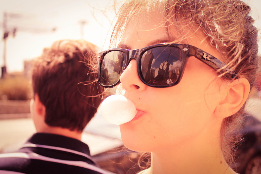 Teenage girl in foreground wearing sunglasses, blowing a gum bubble. Boy in background.