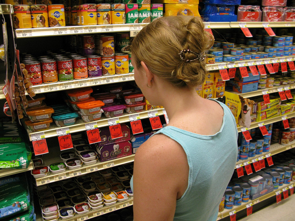View of woman from behind, standing in front of grocery store shelves looking at dog food selection.