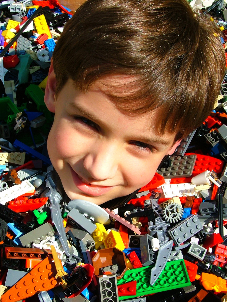 A photo of a young boy literally up to his neck in LEGOs.