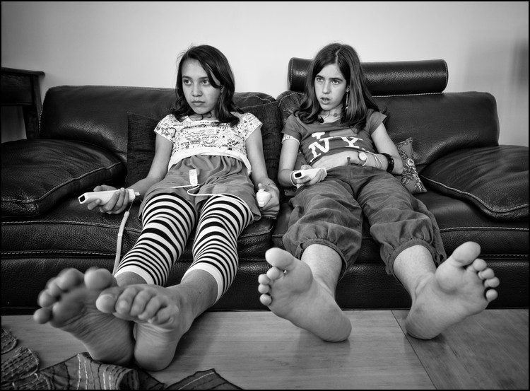 Black-and-white photo of two teenage girls lounging on couch, TV remotes in hand. Caption is Couch Potatoes.