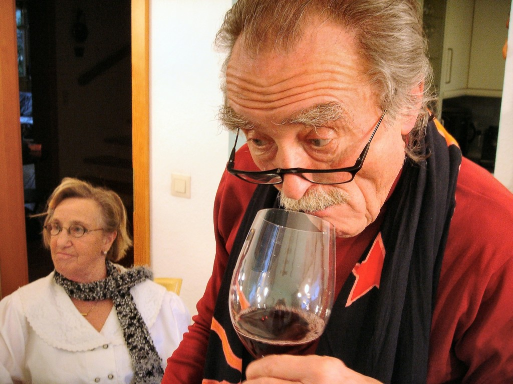 Picture of an elderly man sniffing a glass of red wine. A woman is in the background.