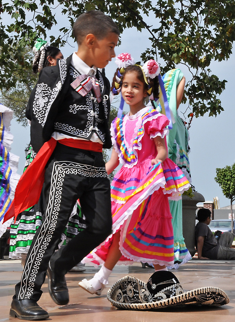 A young Mexican boy and girl dressed in fancy traditional costumes dance.