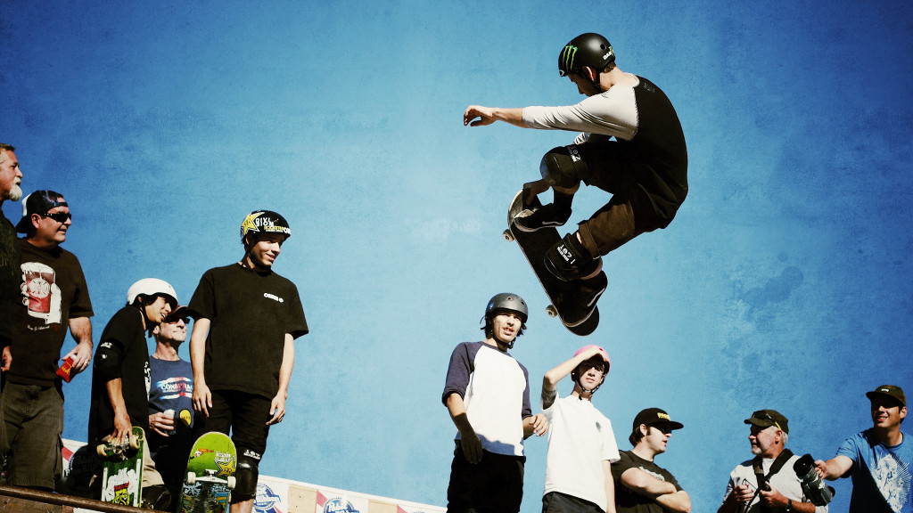 A group of skateboarders watch as another skateboarder performs an aerial stunt.