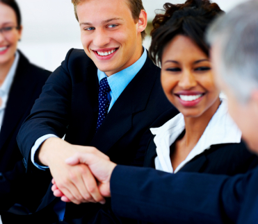 Photo of a man in a suit smiling and shaking hands with another man. A woman in a suit is in between them, also smiling.