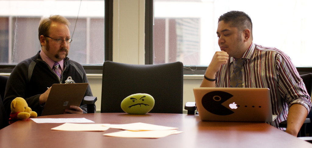 "Two men are seated in a meeting room; both look frustrated. In between them is a chair for the boss, who is absent, but is represented by a small green pillow on the table with a ""frowny face."""