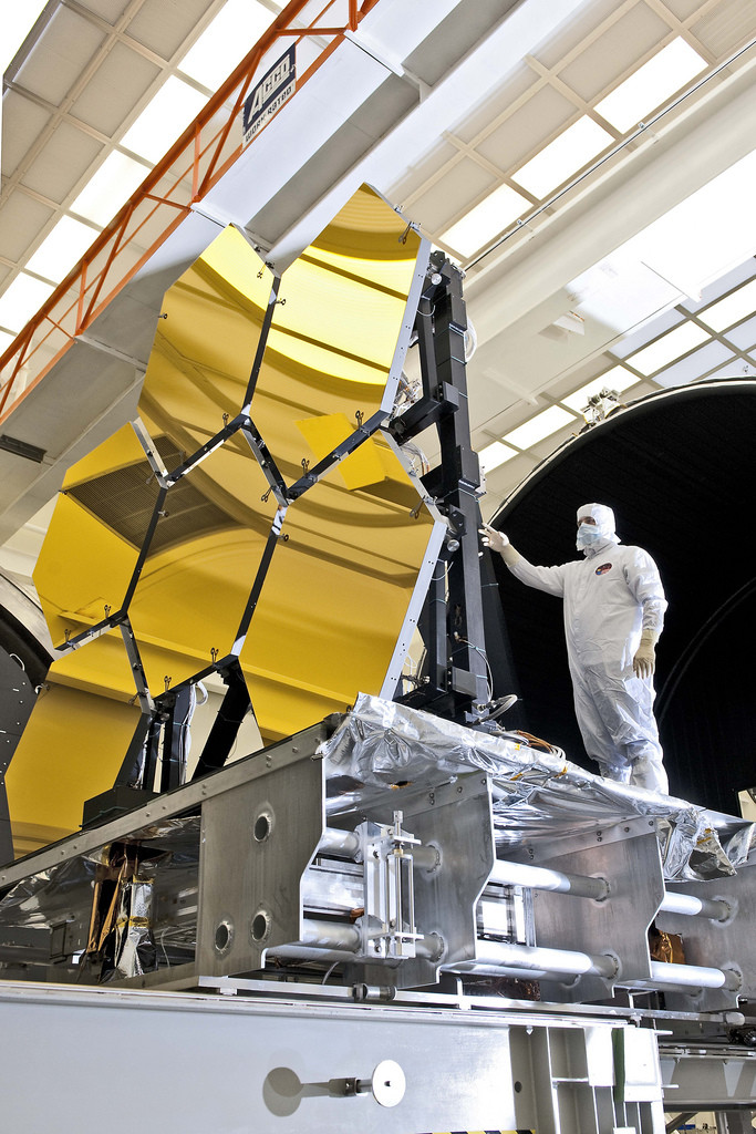 Photo inside NASA space flight center. Man in a white protective suit is holding on to part of the structure that contains six mirror segments for the James Webb Space Telescope.