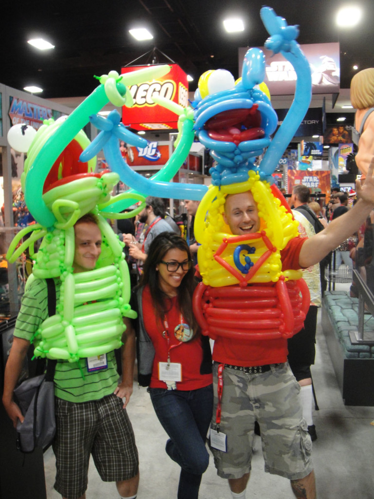 Two young guys pose on either side of a young woman. The guys are wearing colorful Kermit the Frog and Gonza costumes constructed out of balloons. The three are attending the San Diego Comic Convention.