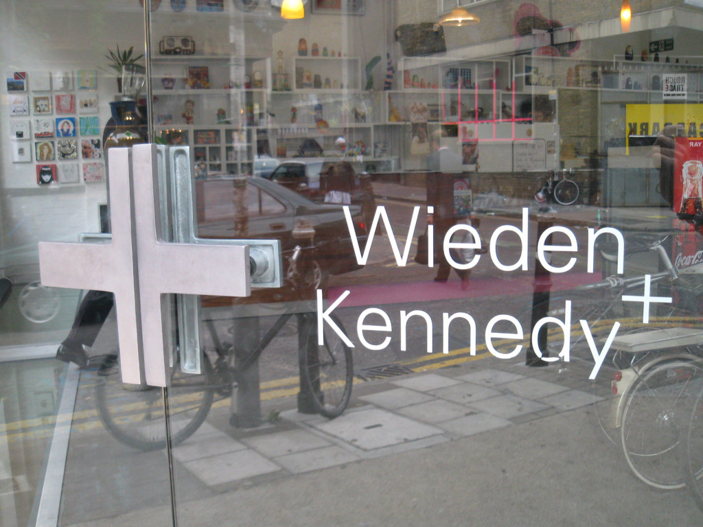 Photo of glass front door to Wieden + Kennedy building. Small shelves filled with objects are visible through the door; so is the reflection of the sidewalk and street out front—a bike and parking meter are visible.