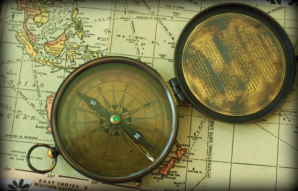 A vintage brass compass lies atop a vintage map.