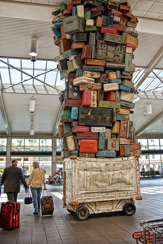 A canvas trolley is stacked so high with lost luggage that it reaches all the way to the ceiling of an airport.