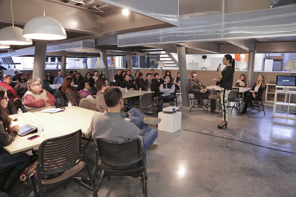 A group of people in a meeting listening to a woman with a microphone.