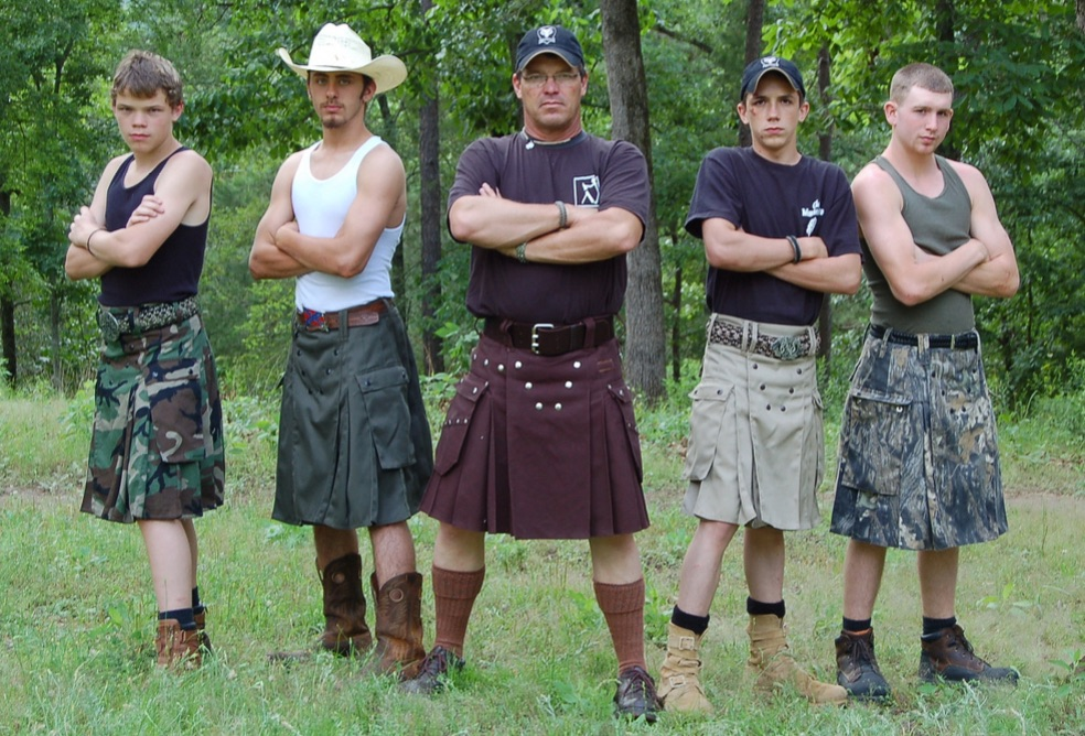 Five men wearing utilikilts and facing the camera, their arms crossed in front of their chests.