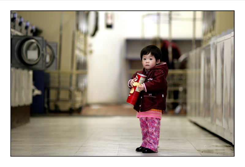 A small child clutching a can of Pringles.