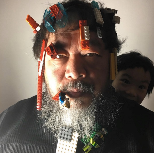 A man with lego blocks stuck to his hair and beard.