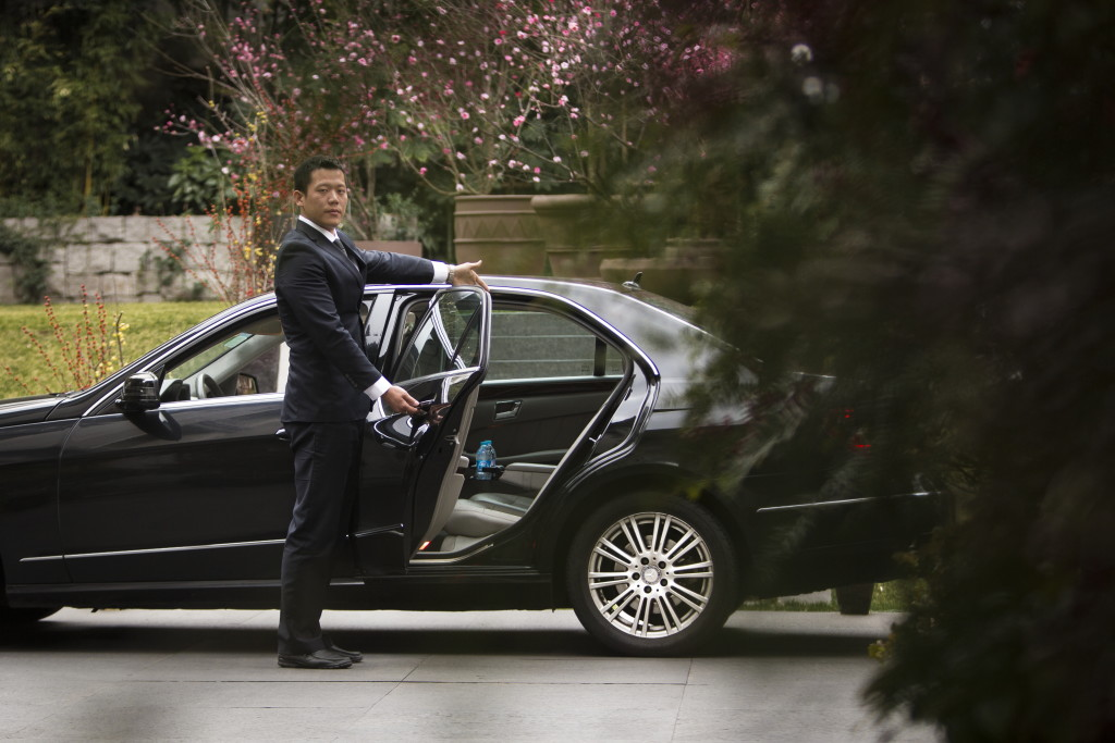 An Uber driver dressed in a suit stands beside a an elegant black sedan, opening the back door. Shanghai, China.