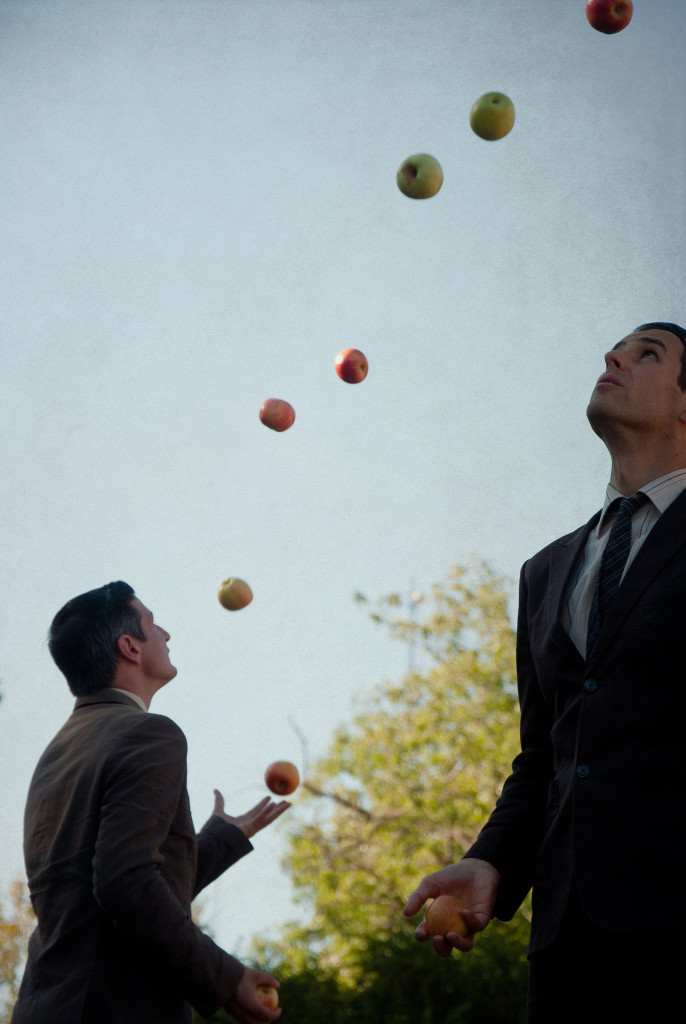 Two men in suits, seen in profile, juggling apples.