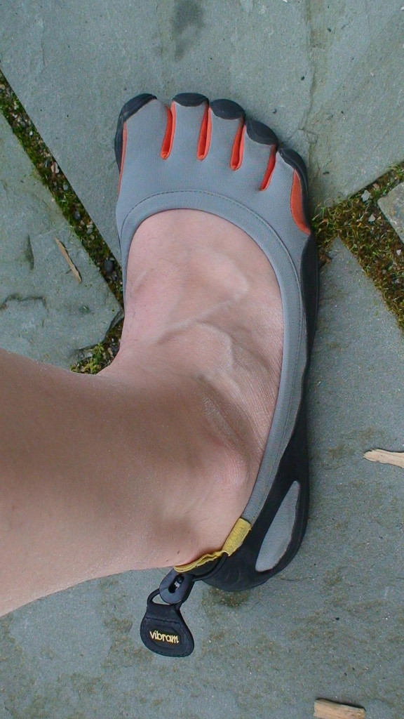 "Photo of a man's leg and foot. He's wearing a gray Five Fingers shoe, which ""fits hims like a glove."""