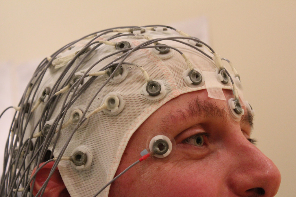 "Photo of the upper half of a man's head is shown. He's wearing a mesh fabric cap with multiple electrodes connected to it. The photo title is ""Volunteer Duty—Psychological Testing"""