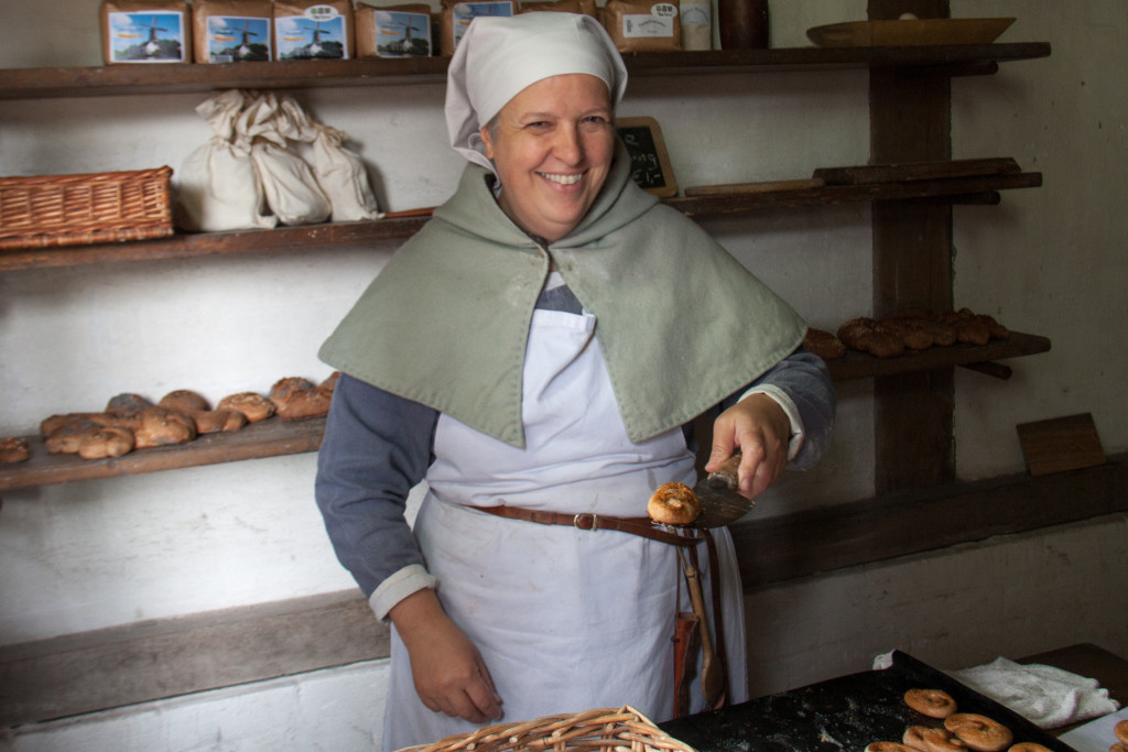A woman holding bread and surrounded by bread. She wears a chef's hat, an apron, and a short cape.