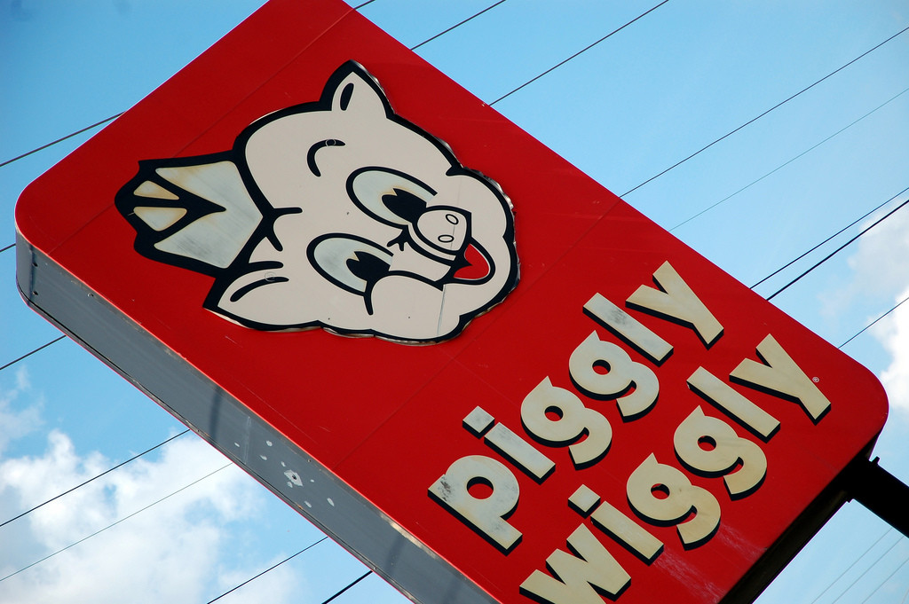 A sign that says Piggly Wiggly and features a cartoon image of a pig's face.