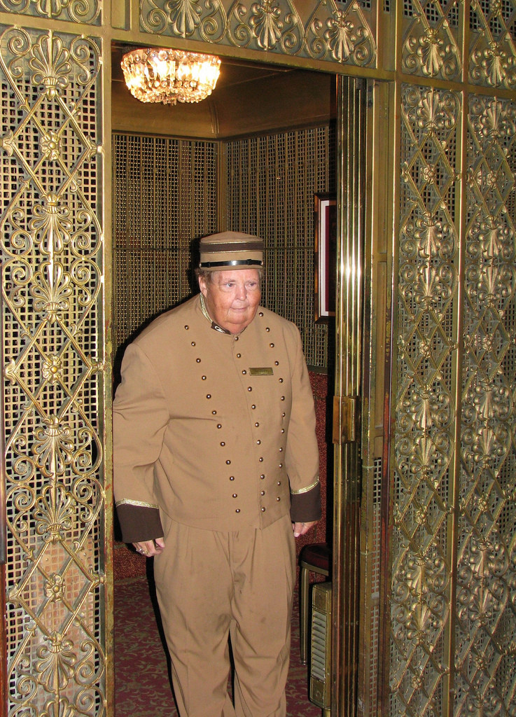 An elevator operator standing in an elevator