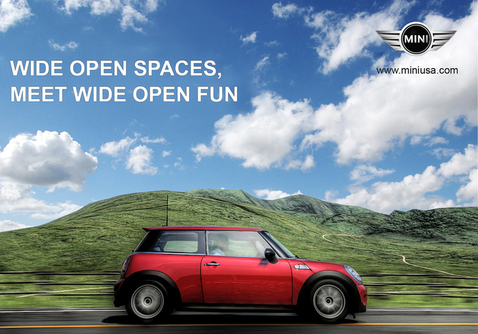 A Mini car drives down a road on a beautiful sunny day by some scenic hills. Text says Wide Open Spaces, Meet Wide Open Fun.