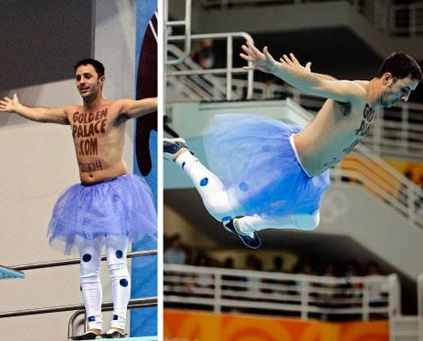A shirtless man wearing a tutu and polka-dotted tights leaps off a diveboard. The words GoldenPalace.com 2004 are painted on his bare chest.