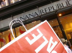 Photo of Banana Republic storefront. In foreground, partial view of a large red shopping bag, with the word SALE printed in white.