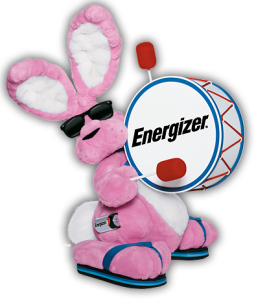 A stuffed pink bunny wearing sunglasses and beating a drum.