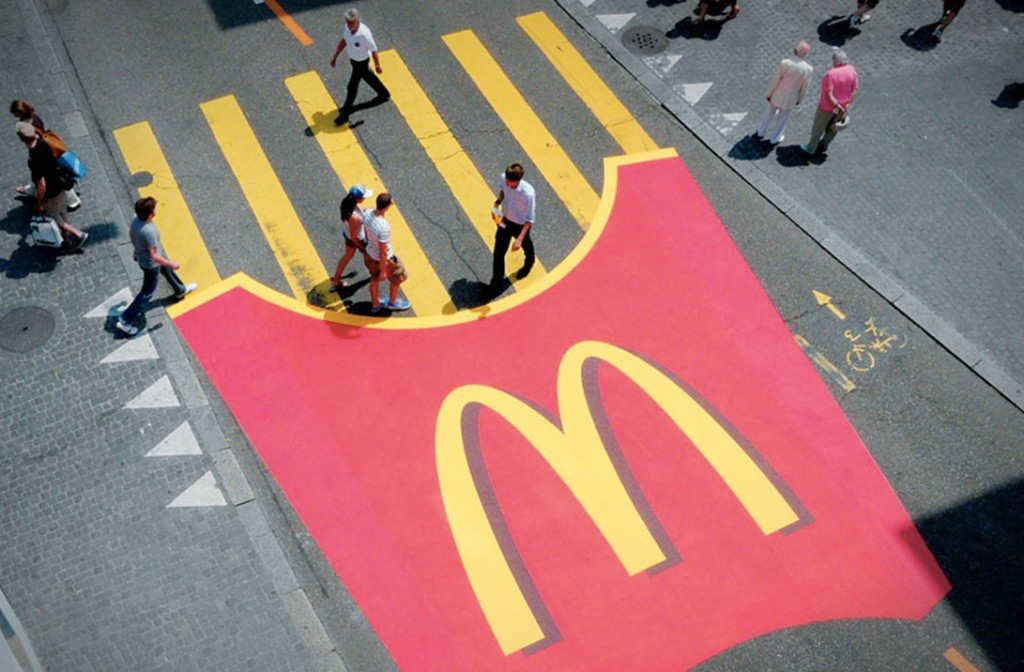 A McDonald's fries container is painted on the street near the yellow stripes of a crosswalk so that the crosswalk stripes appear to be fries.