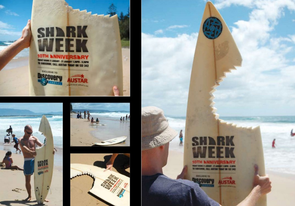 Pictures of a surfboard on a beach with a jagged chunk ripped out so that it looks like a shark chomped on it. The surfboard says Shark Week 10th Anniversary and has more details about the event.