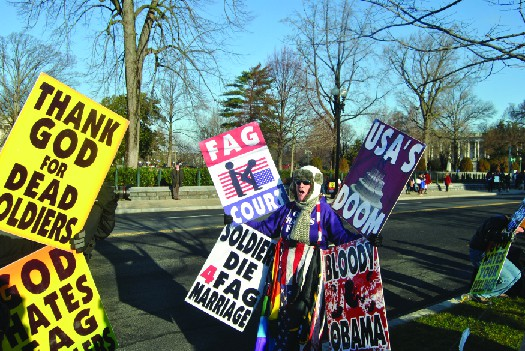 A photo of people holding signs. The signs read