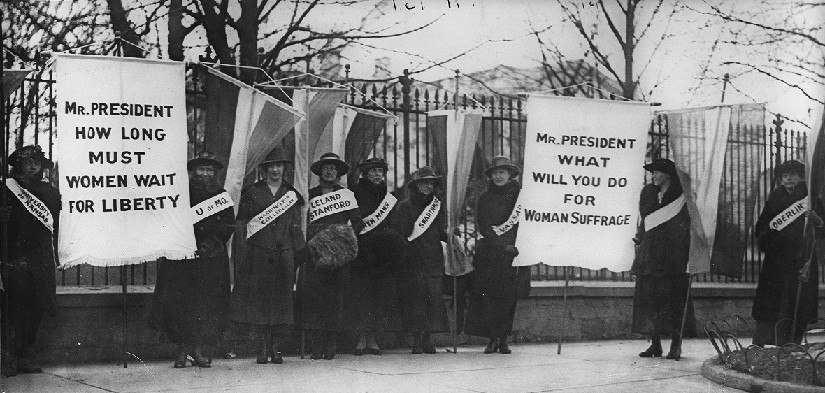 An image of several people standing in front of a fence. Some people are holding banners. The banners read