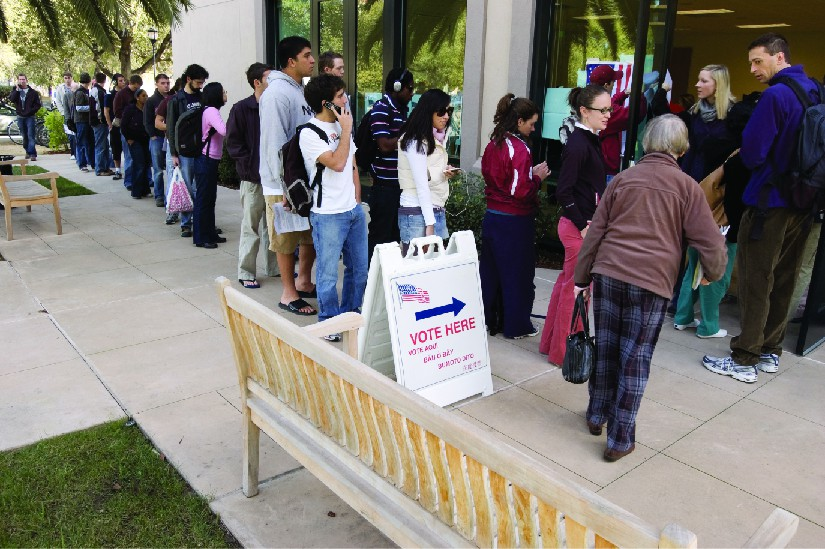 An image of several people standing in line outside of a building. A sign near the front of the line and the building entrance reads