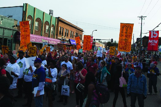 An image of a group of people marching down a street, one of whom holds a sign that reads